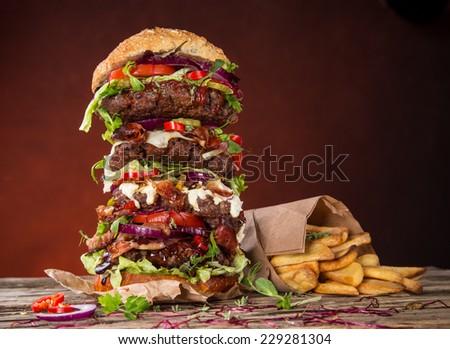 Delicious big hamburger on wooden background - stock photo