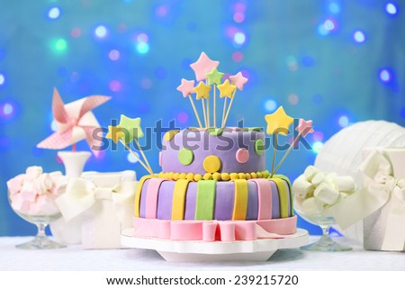 Delicious birthday cake on shiny blue background - stock photo
