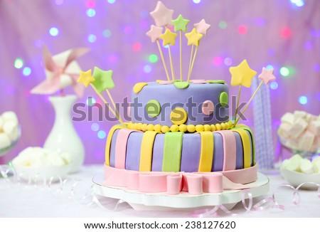 Delicious birthday cake on shiny pink background - stock photo