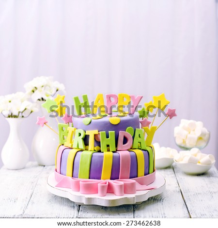 Delicious birthday cake on table - stock photo
