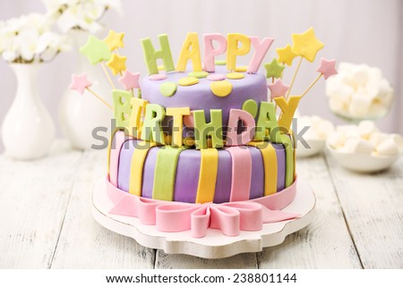 Delicious birthday cake on table on light background - stock photo