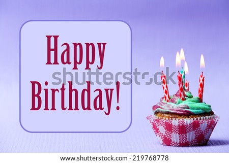 Delicious birthday cupcake on purple background