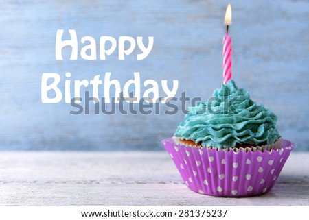 Delicious birthday cupcake on wooden background