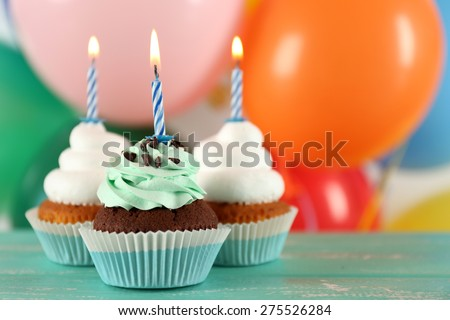 Delicious birthday cupcakes on table on bright background - stock photo