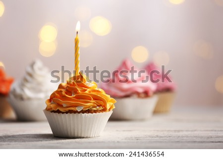Delicious birthday cupcakes on table on light background - stock photo