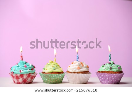 Delicious birthday cupcakes on table on pink background - stock photo
