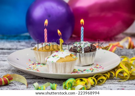 Delicious birthday cupcakes with candles on a wooden table on bright background - stock photo