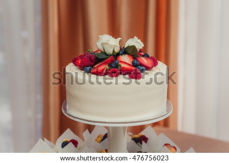 Delicious biscuit cake with fresh strawberries, raspberries, blueberries. Birthday or wedding celebration
