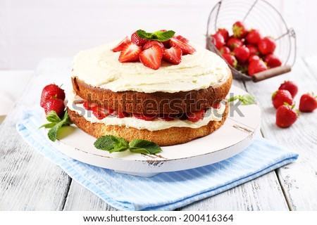 Delicious biscuit cake with strawberries on table on light background - stock photo