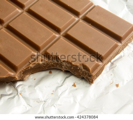 delicious bitten chocolate bar on foil packaging - stock photo