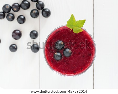 Delicious black currant smoothie with fresh berries on white wood background. Top view or flat lay - stock photo