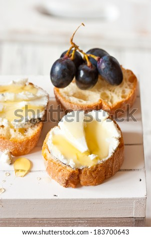 Delicious blue cheese crostini appetizer with honey and grape.