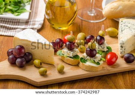 Delicious blue cheese with olives, grapes and salad, behind wine, olive oil, baquettes