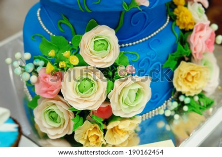 Delicious blue wedding cake decorated with pink and yellow cream roses  - stock photo