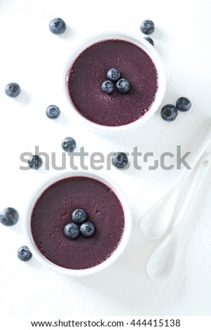 Delicious blueberry mousse in bowls on wooden table - stock photo