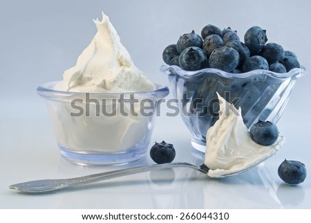 Delicious bowls of ripe blueberries and whipped cream - stock photo