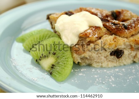 Delicious bread and butter pudding dessert with kiwi fruit and cream. - stock photo