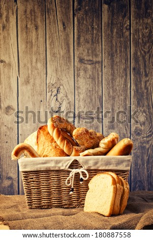 Delicious bread and rolls in wicker basket on kitchen table