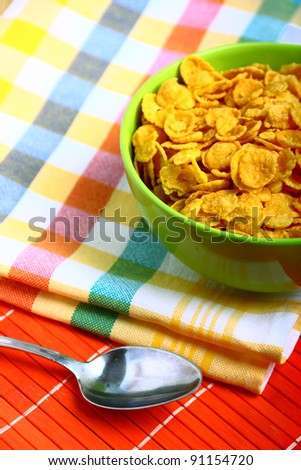 Delicious breakfast corn flakes in green bowl - stock photo