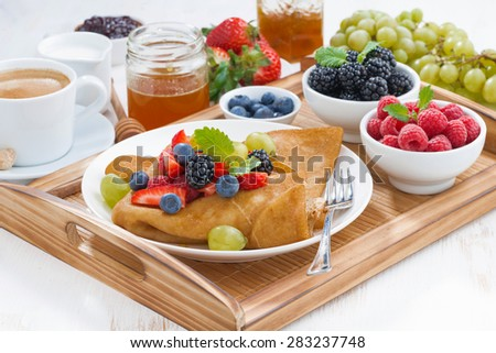 delicious breakfast - crepes with fresh berries and honey, horizontal - stock photo