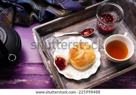 delicious breakfast, crispy bread, raspberry jam and tea  - stock photo