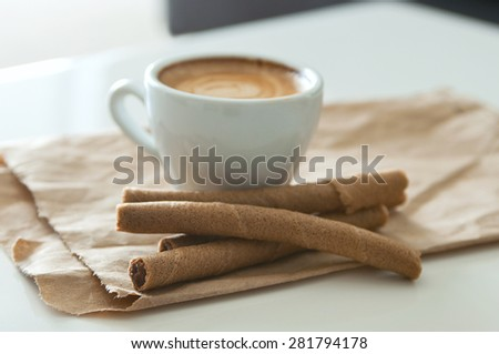 Delicious breakfast cup of strong aroma espresso coffee and chocolate wafer tubes on a recyclable brown paper. Selective focus, main focus on a front wafer tube - stock photo
