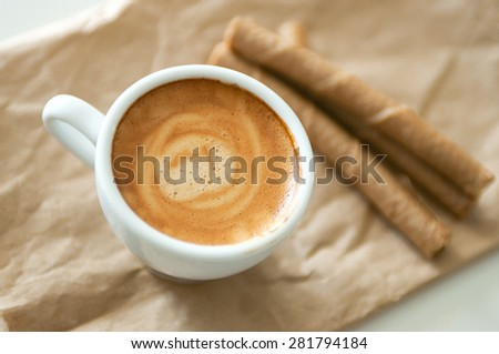 Delicious breakfast cup of strong aroma espresso coffee and chocolate wafer tubes on a recyclable brown paper. - stock photo