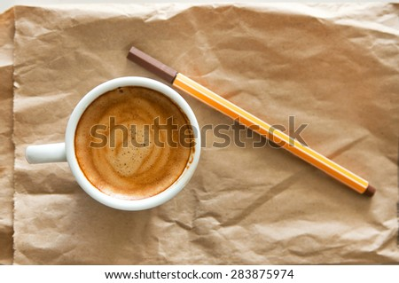 Delicious breakfast cup of strong aroma espresso coffee with brown ink pencil on a recyclable brown paper, copy space - stock photo