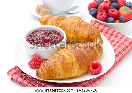 delicious breakfast - fresh croissant with raspberry jam, coffee and berries, isolated on white