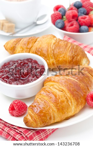 delicious breakfast - fresh croissant with raspberry jam, coffee and berries on white