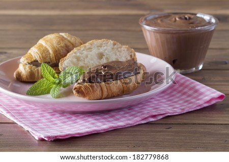 Delicious breakfast of croissant with chocolate cream on a pink checkered napkin. A bowl, a plate and mint. - stock photo