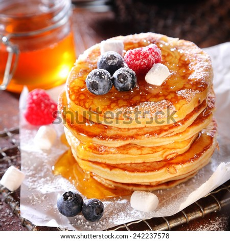 Delicious breakfast of fruity berry pancakes pile in a stack and drizzled with syrup and sugar with fresh blueberries and raspberries