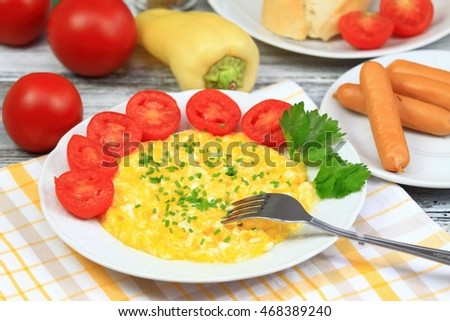 Delicious breakfast of scrambled eggs, baguettes  and vegetable decorated with chopped chives on the plate
