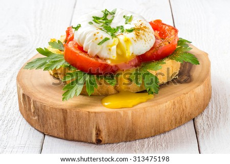 Delicious breakfast on white wooden background: poached egg on toast with tomato and parsley on a thick wooden plate  - stock photo