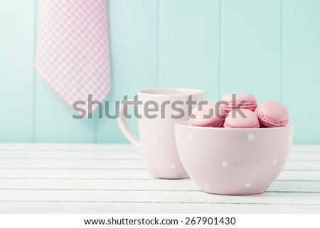Delicious breakfast: some macarons (macaroons) in a bowl and a pink polka dots mug on a white wooden table. Vintage scene - stock photo