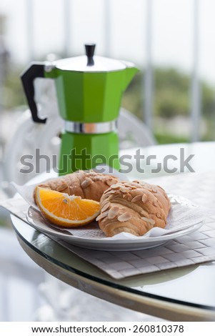 Delicious breakfast with coffee on hotel's balcony, fresh croissants and slice of orange fruit with   coffee percolator background - stock photo