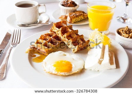 Delicious breakfast with coffee, orange juice, waffles, egg, cheese and honey - stock photo