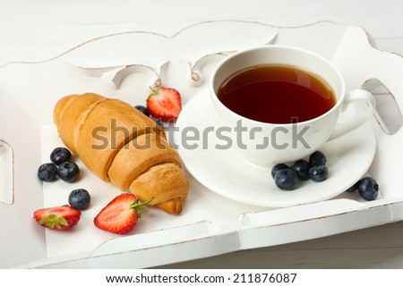 Delicious breakfast with cup of tea, fresh croissant and berries