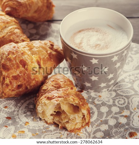 Delicious breakfast with fresh croissants and cup of cappuccino on grey wooden background. Selective focus. Toned square image - stock photo