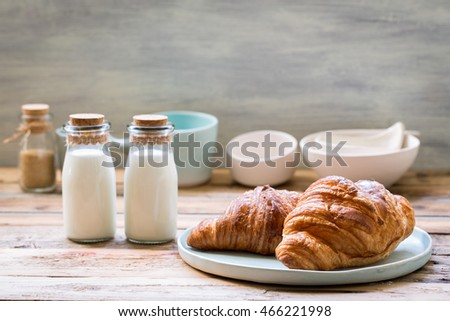Delicious breakfast with fresh croissants and milk on old wooden background