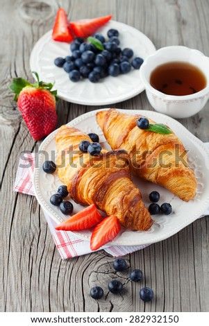 Delicious breakfast with fresh croissants and ripe berries on old wooden background, top view - stock photo