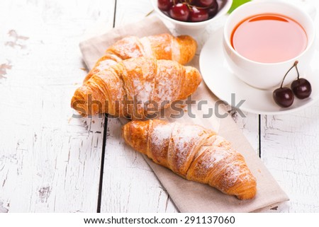 Delicious breakfast with fresh croissants and ripe cherries on white wooden background. Selective focus - stock photo