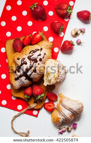 Delicious breakfast with fresh croissants and strawberries on white wooden background.