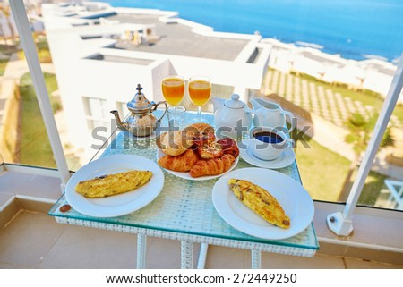 Delicious breakfast with omelet, pastry, coffee and mint tea served on the balcony with sea view in Moroccan hotel - stock photo