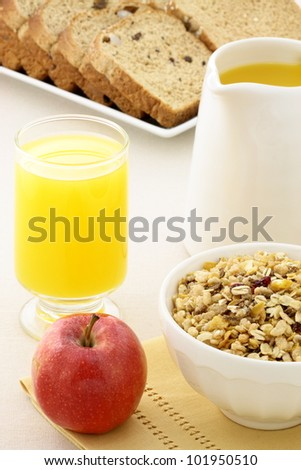 delicious breakfast with orange juice, red apple, whole grain bread and a healthy bowl of muesli cereal. - stock photo