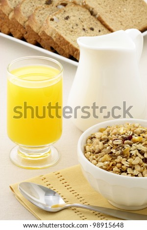 delicious breakfast with orange juice, whole grain bread,milk and a healthy bowl of cereal. - stock photo