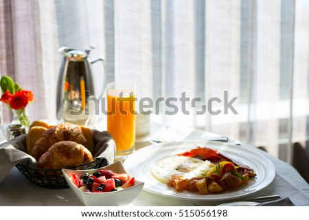 delicious breakfast with pastries, eggs, fruits and juice served in hotel room, in-room dining, contrast view, hospitality and vacation concept