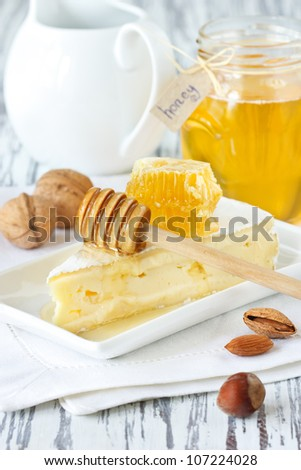 Delicious brie with honeycombs and nuts on a linen napkin.