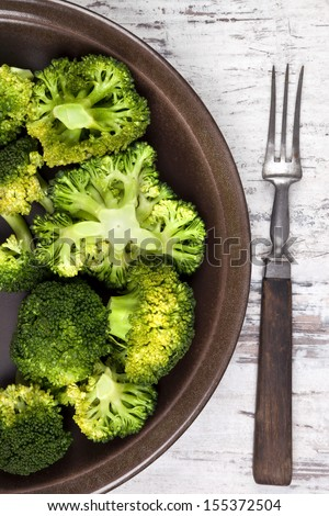 Delicious broccoli on brown plate with fork on white wooden background, top view. Healthy vegetable eating.  - stock photo