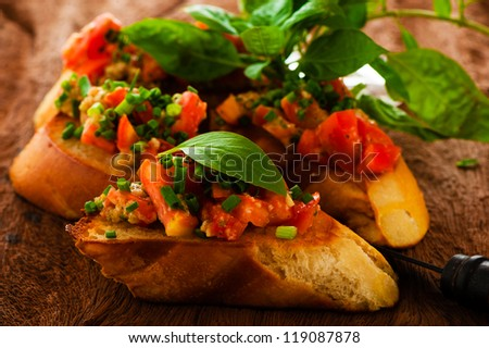 delicious bruschetta appetizer on wooden board - stock photo